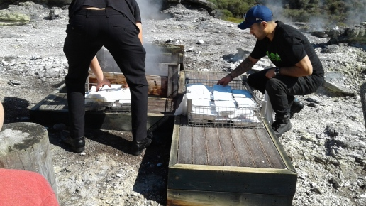 Putting Maori hangi meals into the cooking box